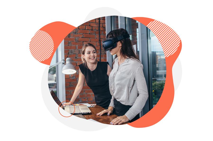 Two women in office, one wears a vr headset